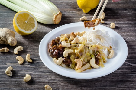 exotically: Lemon chicken with noodles and cashew on wooden table