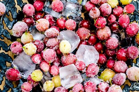 alimentos congelados: Grosellas congeladas con cubitos de hielo en una placa de la vendimia