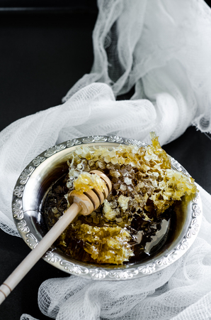 stirrer: honeycomb in a vintage bowl with white fabric on black background