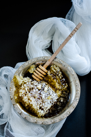 stirrer: Top wiev of honeycomb in a vintage bowl with white fabric on black background Stock Photo