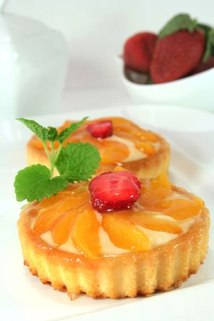 confiserie: Apricot tart with fresh strawberries on a plate