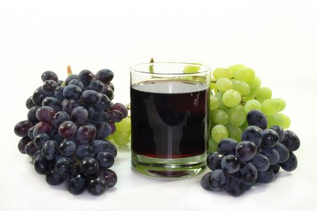 a glass of grape juice with light and dark grapes