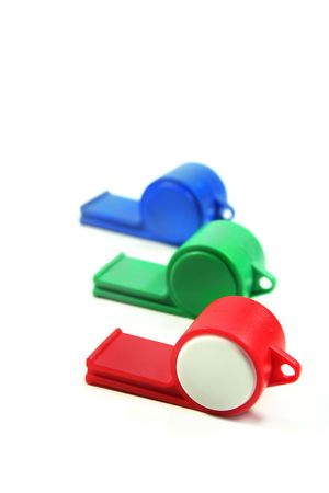 arbitrator: three colored whistles on a white background