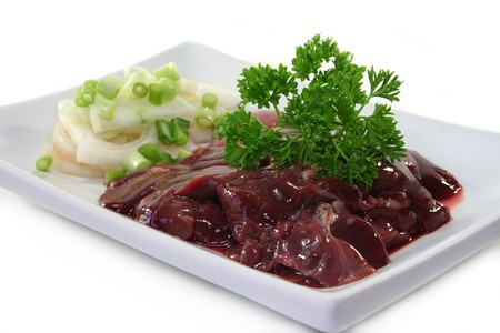 giblets: raw liver with onions and parsley on a white plate Stock Photo