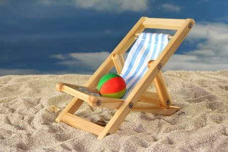 Deck chair and a water polo on a sandy beach Stock Photo - 7226877