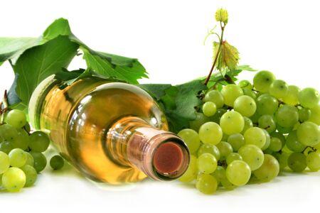 white wine bottle: Una botella de vino blanco con uvas y hojas  Foto de archivo