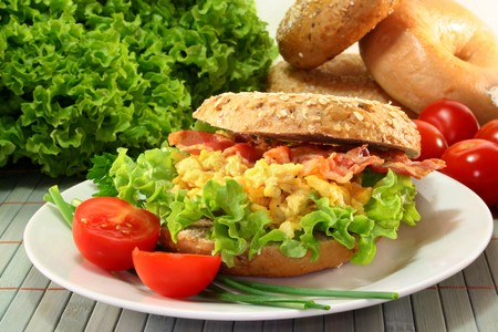 Bagel with salad, scrambled eggs and crispy bacon photo