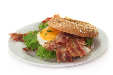 Bagel with salad, fried egg and crispy bacon photo