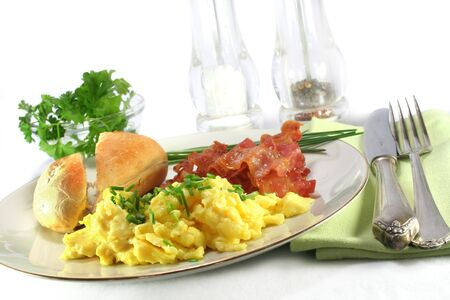 scrambled eggs: un plato de huevos revueltos con bacon  Foto de archivo