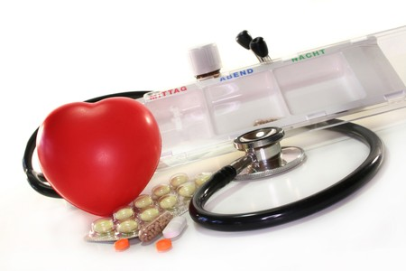 Stethoscope and pills against white background photo
