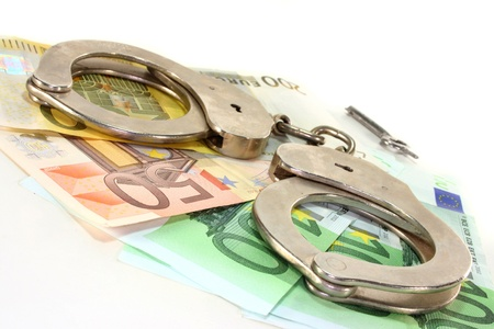 tax evasion: Euro notes and handcuffs ion a white background Stock Photo