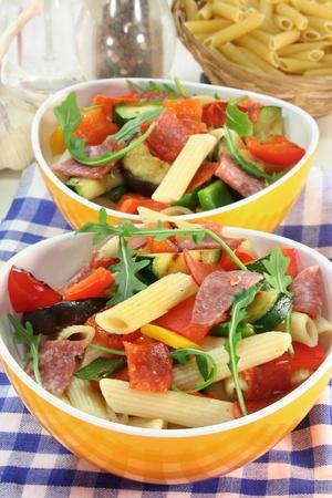 Pasta salad with roasted mediterranean vegetables and arugula Standard-Bild