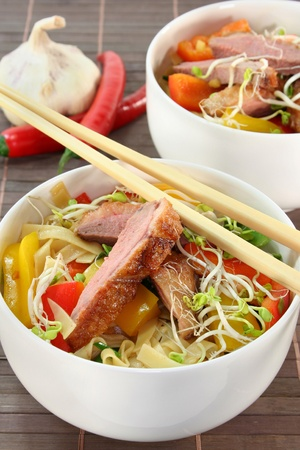 crispy duck breast with fried noodles and vegetables