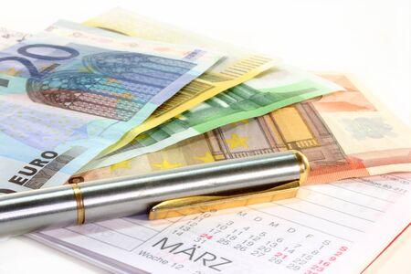 billets euros: de nombreux billets en euros et un stylo sur un calendrier