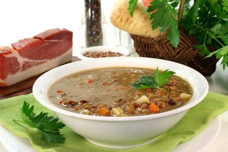 a bowl of lentil soup with bacon and parsley