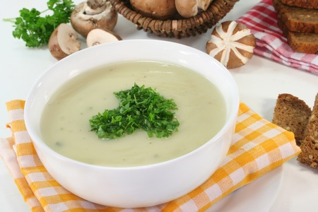 a bowl of Cream of mushroom soup with fresh ingredients photo