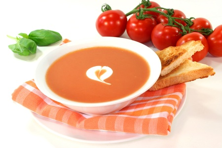a bowl of tomato cream soup with toast