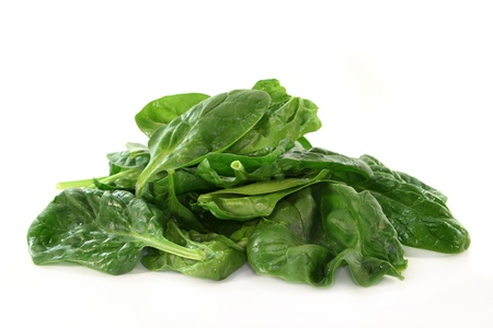 fresh spinach: a handful of spinach on a white background