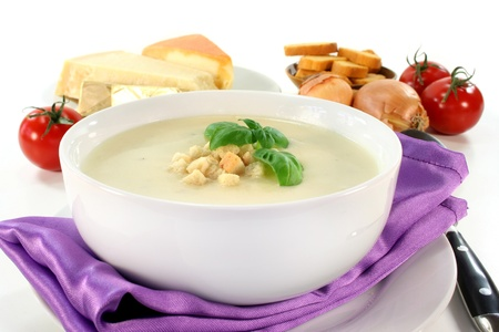 parmesan cheese: a bowl of cheese cream soup with croutons and basil Stock Photo