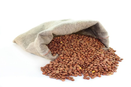 dried lentils in a jute sack on a white background
