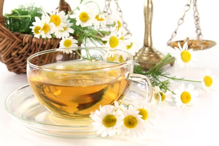 a cup of chamomile tea with fresh flowers