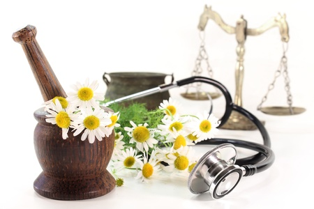 remedies: Stethoscope on a white background and chamomile