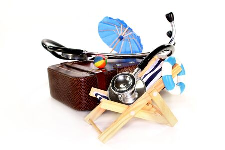 health insurance: a suitcase, deckchair and stethoscope against white background