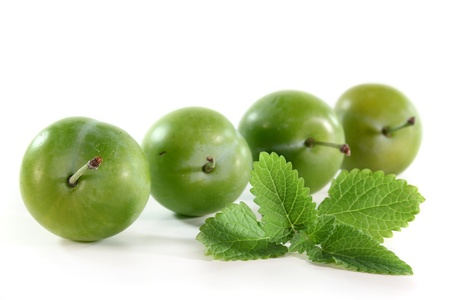 fresh green plums on a white background