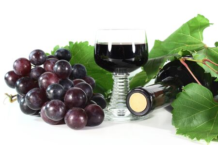 a bottle of red wine and fresh grapes on a white background photo