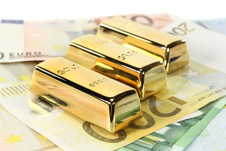 Gold bars and Euro notes on a light background