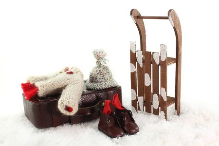 ropa de invierno: Trineo, ropa de invierno y las maletas delante de fondo blanco