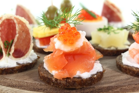 canapes: different canapes on a wooden board on a white background