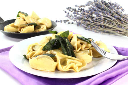 pine nuts: Tortellini with fried sage leaves and pine nuts Stock Photo