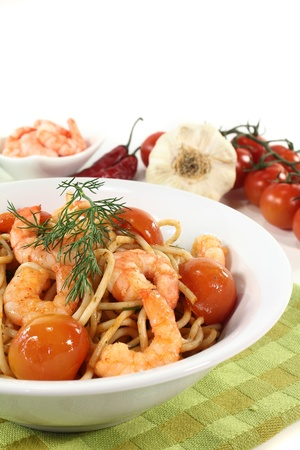 spaghetti with shrimps, tomatoes and dill photo