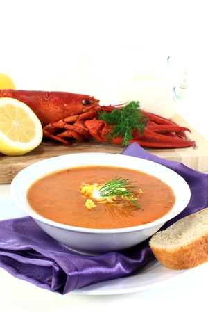a bowl of lobster soup with dill and lemon photo