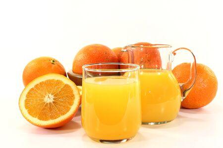 a glass of orange juice and fresh oranges photo