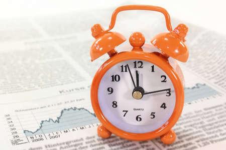 financial newspaper: an alarm clock on a financial newspaper Stock Photo