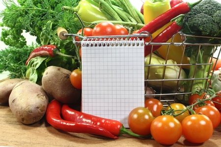 shopping list: a checkered note pad and various vegetables Stock Photo