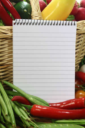shopping list: Ruled note pad and a variety of vegetables Stock Photo
