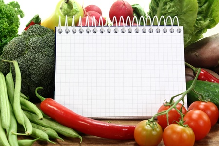 recipes: a checkered note pad and various vegetables Stock Photo