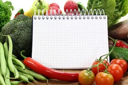 un bloc de notas a cuadros y diversas hortalizas