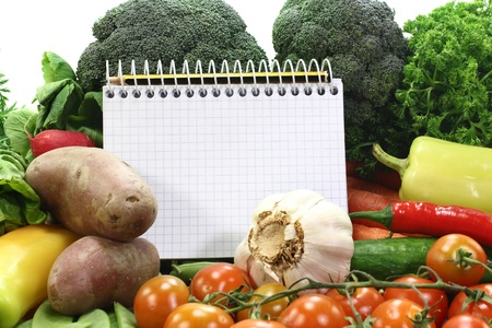 a checkered note pad and various vegetables