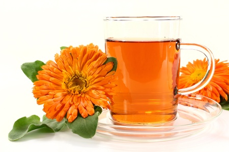 a glass of marigold tea and calendula flowers on a bright background