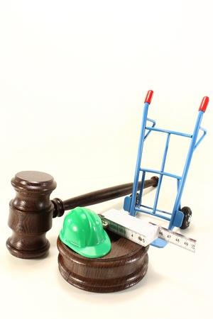 despido: jueces martillo con casco de construcci�n in situ, y palo de un metro de doble sobre un fondo claro Foto de archivo