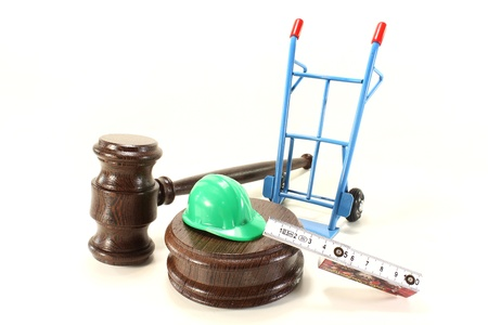 buildingsite: judges gavel with building-site helmet and double meter stick on a light background
