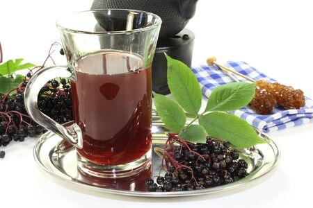 umbel: a glass of elderberry tea with fresh elderberries