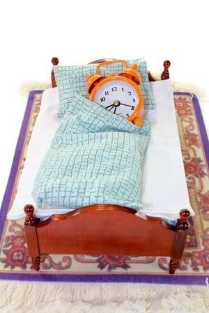 restlessness: a wooden bed and alarm clock on a white background Stock Photo