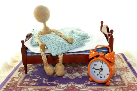 a wooden bed and alarm clock on a white background Stock Photo
