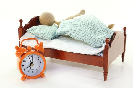 arousing: a wooden bed and alarm clock on a white background Stock Photo