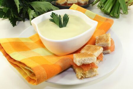 a bowl of Cream of celery soup with salmon croutons photo